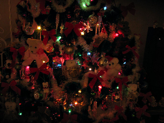 Closer photo of Christmas tree decorated with bears all lit up